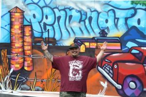 Nationally known graffiti artist Leon Rainbow with the Pennington Day 2015 mural
