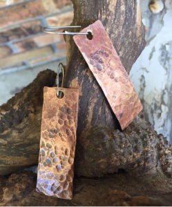 Jewelry artist Barb Eldridge hammered copper earrings at the Hopewell Valley Arts Council tent at the Pennington Farmers Market